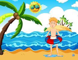 Man med en floaty på stranden