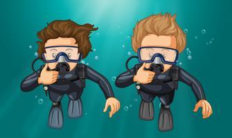 Två dykare gör hand gest under vatten