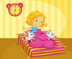 Ein Mädchen, das am Bett mit zwei Kätzchen aufwacht
