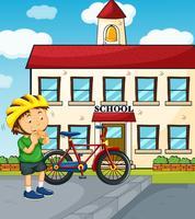 Skolplats med pojke och cykel
