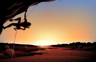 En solnedgång över öknen med en man som klättrar vid trädet