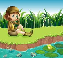 Ein Mädchen, das einen Hut trägt, der am Flussufer sitzt