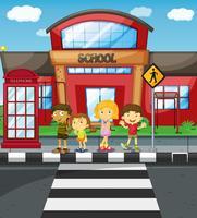 Barn väntar på att korsa vägen framför skolan vektor
