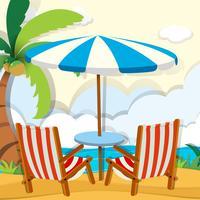 Stühle und Sonnenschirm am Strand
