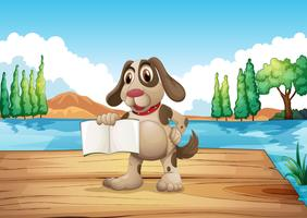 En hund som håller en tom bok som står vid hamnen