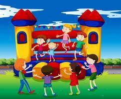 Barn studsar på lekhuset