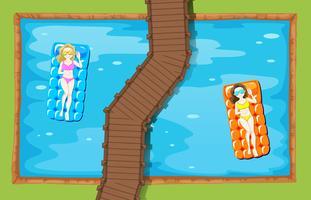 Två kvinnor på flytande matta i poolen