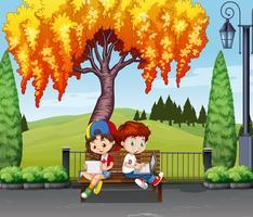 Pojke och flicka sitter under trädet