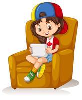 Liten tjej med tablett sitter på stol