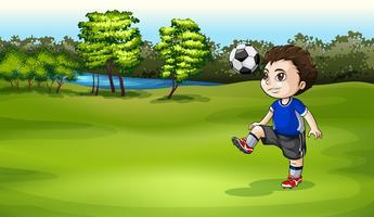 En pojke som spelar fotboll utomhus