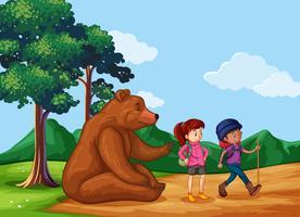 Stor björn sitter på marken och folk går på vandring
