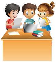 Kinder, die an Computer auf dem Schreibtisch arbeiten