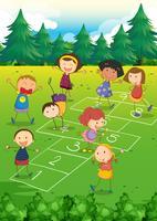 Barn leker hopscotch i parken
