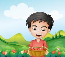 Ein Junge hält einen Korb mit Erdbeeren
