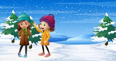 Två tjejer står på snöfältet