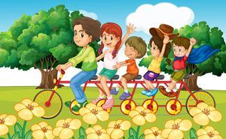Föräldrar och barn cyklar i parken