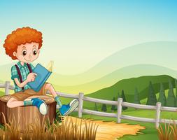Liten pojke läser bok på fältet