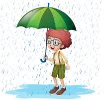Liten pojke står i regn