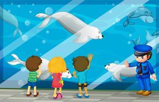 Barn tittar på fisk på akvariet