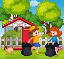 Glückliche Mädchen, die Abfall am Garten sammeln