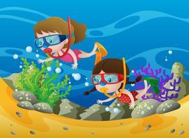 Zwei Mädchen, die unter dem Ozean tauchen