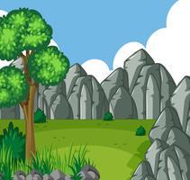 Bakgrundsscen med grönt fält och steniga berg