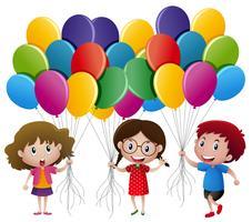 Tre barn håller ballonger
