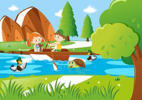 Pojke och flicka roddbåge i floden