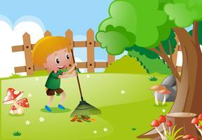 Liten pojke raking lämnar i trädgården