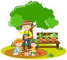 Barn och trädgårdsmästare planterar i trädgården