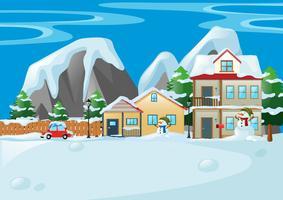 Scen med hus och snögubbe