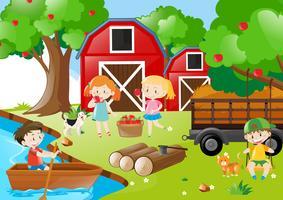 Barn plockar upp äpplen i fruktträdgården