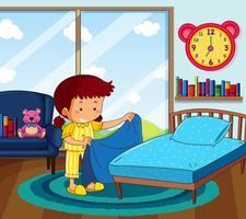 Tjej i gula pyjamas gör säng i sovrummet