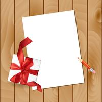 Julbrev med en penna och en gåva röd båge på en träbakgrund