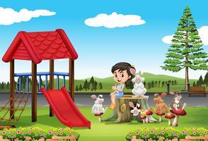 Tjej och kaniner på lekplatsen