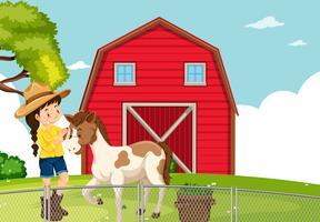 En tjej med häst på jordbruksmark