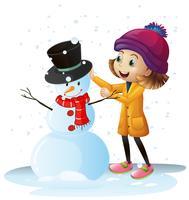 Tjej leker i snö med snögubbe