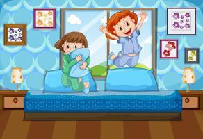 Zwei Mädchen in den Pyjamas, die auf Bett springen
