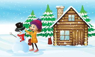 Kleines Mädchen, das Schneemann auf dem Gebiet macht