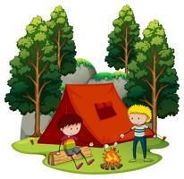 Två pojkar camping i skogen