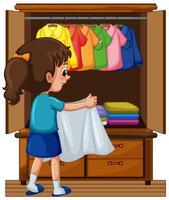 Tjej sätta i kläder i garderoben