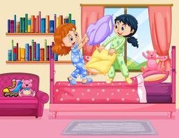 Två tjejer kuddar slåss i sovrummet