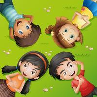 Fyra barn ligger på grönt gräs