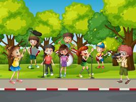 Pojke skjuter sina vänner som sjunger i parken