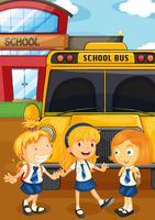 Drei Schüler in Uniform beim Schulbus