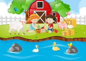 Två barn planterar träd vid floden