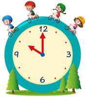 Barn cyklar på jätte klocka
