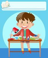 Pojke och skrivbord fullt av utrustning och böcker