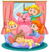 Vier Mädchen, die mit rosafarbenem Bären spielen