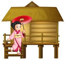 Japanisches Mädchen an der Bambushütte
